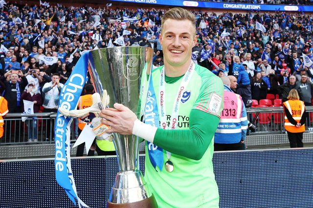 Craig MacGillivray celebrates with the Checkatrade Trophy after Pompey's triumph in March 2019. Picture: Joe Pepler
