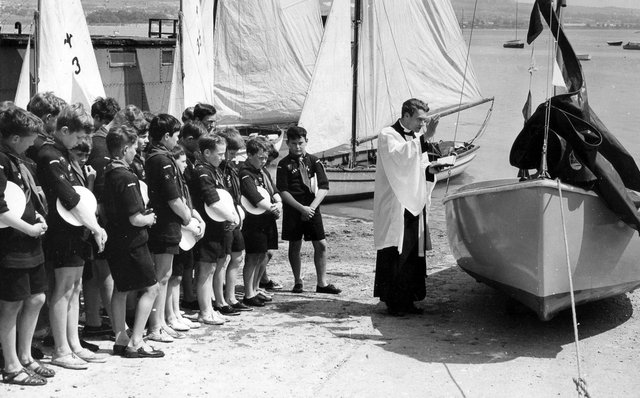 The Vicar of St. Mary's Portchester, the Rev Michael Thomas, dedicates a new dinghy for the Sea Scouts on the slipway at Portchester Sailing Club in 1966.
