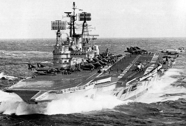 Seen in 1977 is HMS Ark Royal with a flight of Phantom, Buccaneer and Gannet aircraft on her flight deck.