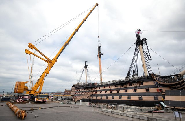 A crane begins the process of removing the main lower mast from HMS Victory at Portsmouth Historic Dockyard in Portsmouth. Picture Andrew Matthews/PA Wire
