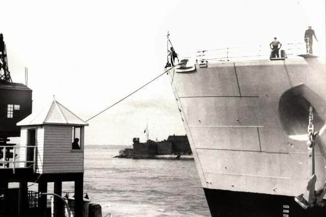 The bow of HMS Vanguard just yards from the old customs watch house. Picture: Courtesy of Deane Clark.