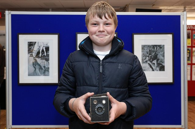 Jack Shields, 14, with some of his work. He is holding a Box Brownie that he bought today to add to his camera collection. Wildlife photography exhibition at the Central Library, Portsmouth. The work is by pupils from The Harbour SchoolPicture: Chris Moorhouse (jpns 200521-01)