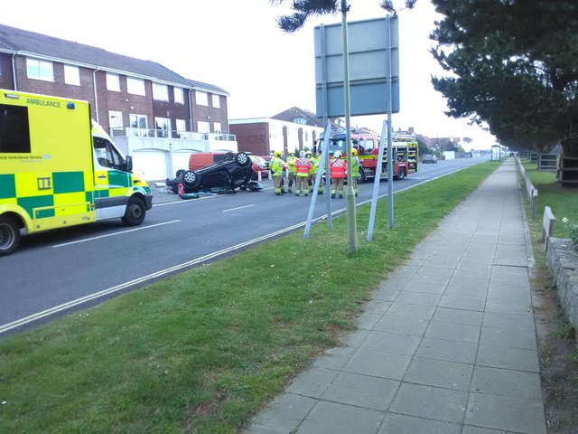 Emergency service crews have been called to a car overturned by a crash along Hayling Island's Sea Front Road.