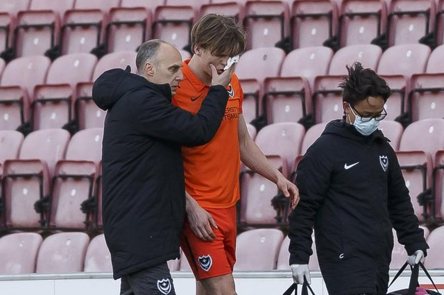 Pompey defender Sean Raggett is helped off the pitch following a clash of heads with Wigan forward Callum Lang.  Picture: Daniel Chesterton/phcimages.com