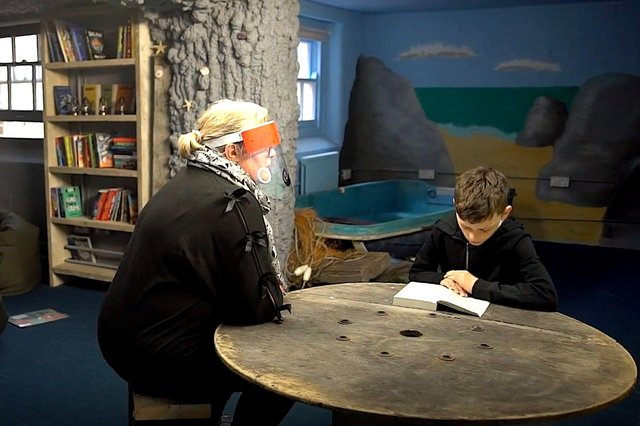 Inside 'The Cave', a volunteer reads with a student from the Pompey Pirates. Picture: Literacy Hubs