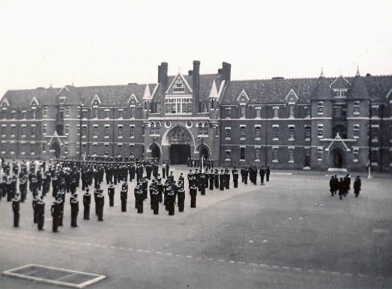 This is a view of Divisions on Victoria Barracks parade ground in 1954. This vista is from the Duchess of Kent Barracks and we see sailors and wrens standing to attention.