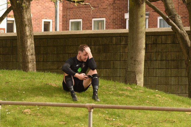 US Portsmouth keeper Tom Price sits alone on a grass bank at one end of the Victory Stadium after his side's FA Vase semi-final loss. Picture: Keith Woodland.