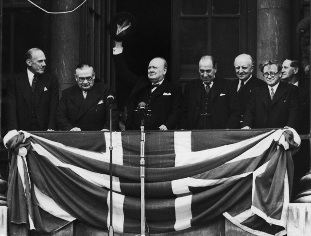 British Prime Minister Winston Churchill addresses the crowds from the balcony of the Ministry of Health in Whitehall on VE Day, on May 8, 1945. From left to right, Ernest Bevin, Churchill, Sir John Anderson, Lord Woolton and Herbert Morrison.  (Photo by Central Press/Hulton Archive/Getty Images)