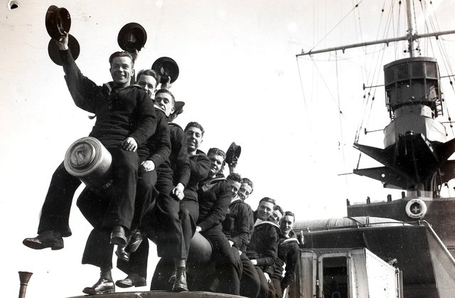 A group of RNVR (Royal Naval Volunteer Reserve) ratings raise a cheer on reaching Plymouth, England on the 'HMS Curacoa'. Officers and ratings of the RNVR (London and Sussex Divisions) are spending Easter afloat - they left Portsmouth for Plymouth and Torbay and are carrying out practical training including gunnery during their cruise. (Photo by Fox Photos/Hulton Archive/Getty Images)