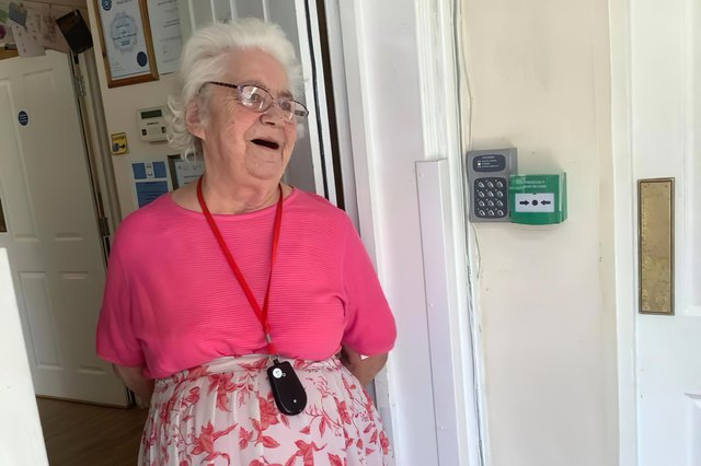 A Hartwell Lodge resident watches through the front door with a smile as Jennifer Parker-Lummis performs in the car park. Picture: Hartwell Lodge