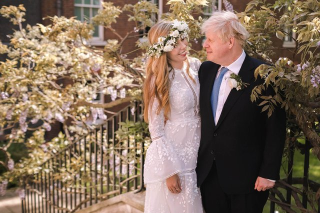 In this handout image released by 10 Downing Street, Prime Minister Boris Johnson poses with his wife Carrie Johnson in the garden of 10 Downing Street following their wedding at Westminster Cathedral, May 29, 2021 in London, England. Photo by Rebecca Fulton / Downing Street via Getty Images.