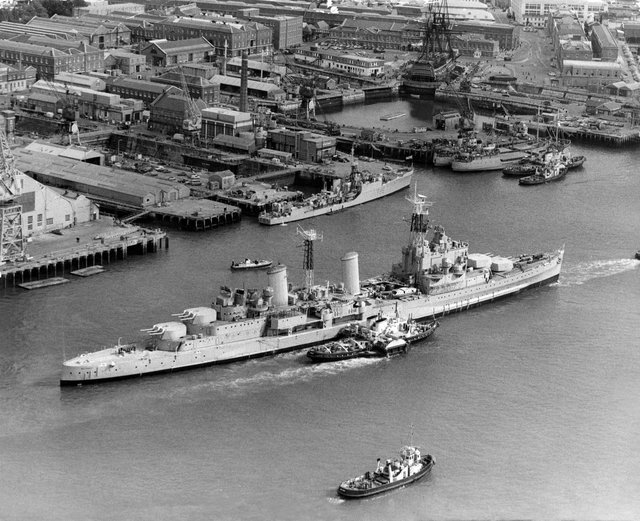 The Royal Navy Town-class light cruiser HMS Belfast under tow from tugboats passes the18th century 104-gun first-rate ship of the line and Admiral Lord Nelson's flagship HMS Victory on her last voyage from Portsmouth Dockyard to her new berth in London as a floating museum on 2 September 1971 in Portsmouth, United Kingdom.  (Photo by Keystone/Hulton Archive/Getty Images).