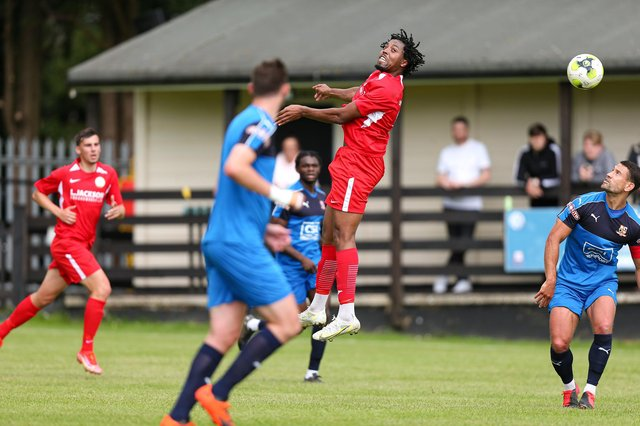 Horndean's Jean-Pierre Alexander (red) in action against Hartley Wintney. Picture: Chris Moorhouse
