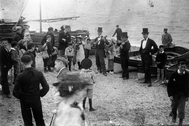 circa 1895:  A trio of musicians attract a small crowd of children on Southsea  beach.  (Photo by F J Mortimer/Hulton Archive/Getty Images)