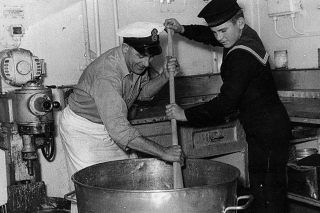 Chief Petty Officer Les Russell and youngest sailor Jerry Locke stirring the Christmas pudding mix in 1949 aboard HMS Theseus, a light aircraft carrier.