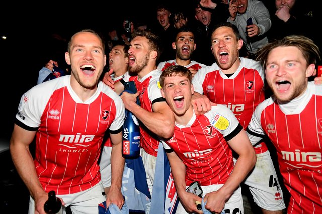 CHELTENHAM, ENGLAND - APRIL 27: Players and fans of Cheltenham Town celebrate their side's victory outside the ground as they gain promotion to the Sky Bet League One after the Sky Bet League Two match between Cheltenham Town and Carlisle United at The Jonny-Rocks Stadium on April 27, 2021 in Cheltenham, England. Sporting stadiums around the UK remain under strict restrictions due to the Coronavirus Pandemic as Government social distancing laws prohibit fans inside venues resulting in games being played behind closed doors.  (Photo by Dan Mullan/Getty Images)