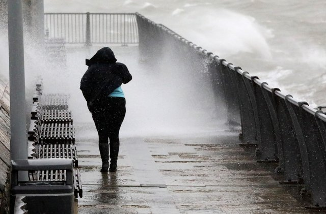 A resident struggles to walk as waves batter the Pompey coastline as Storm Ciara unleashes her wrath.