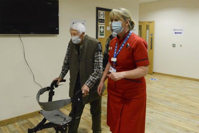 Michael Tibbs, 99, being taken through by Liz Rix, Chief Nurse, to receive his COVID vaccine. Picture: Ewan Galvin/Solent News & Photo Agency