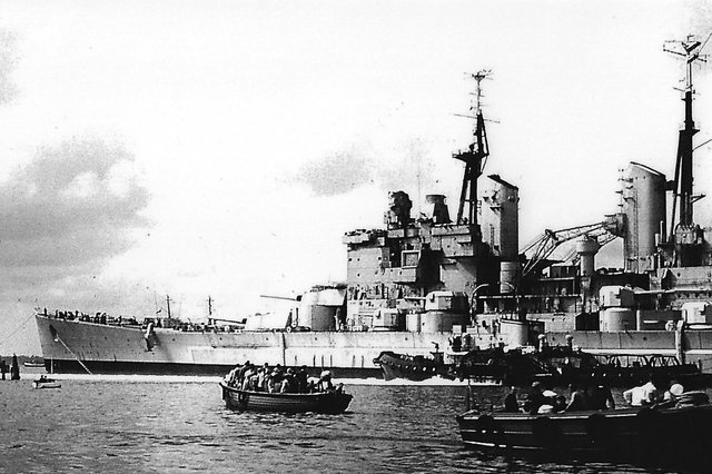 HMS Vanguard with the sea-going tug Advice on the port side attempting to halt her advance into Point. Picture: Barry Cox collection.