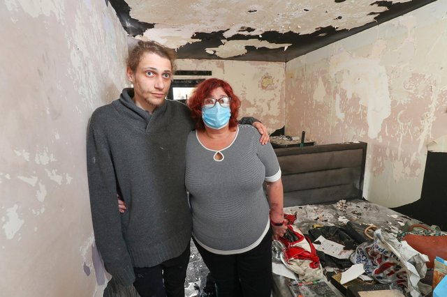 Eve Rendle and her son Michael pictured in their fire damaged home. The are appealing to the community for help in repairing the property as they did not have home insurance. The pair are pictured in Eve's bedroom. Picture: Stuart Martin (220421-7042)