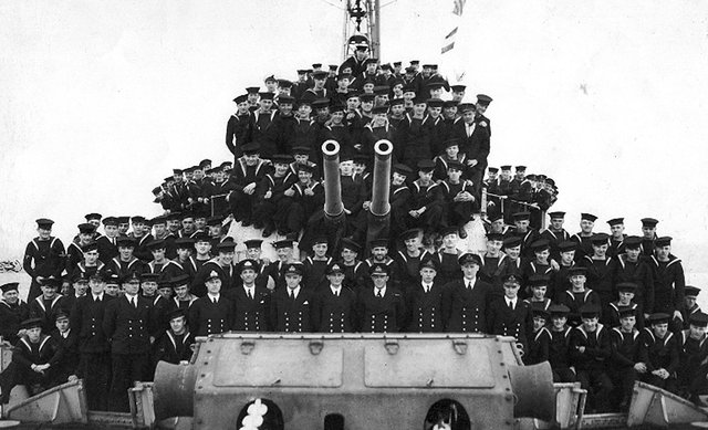 Crew member of HMS Lapwing. Here we see the officers and men of the ship gathered around A & B turrets.