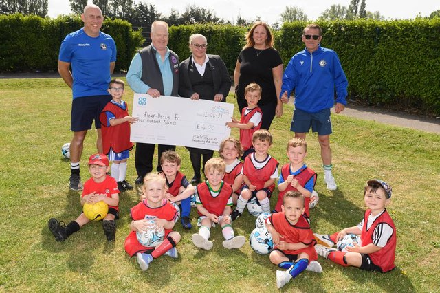 Fleur De Lys receive a £400 cheque from the local Co-op. Back (from left): Jerome Carroll (FDL vice chairman), Dave Brown (Salisbury Road Co-op, Cosham), Sarah Cunningham (Drayton Funeral Care, Co-op), Kerrie Kilford, Steve Jackson (FDL chairman). Also pictured are some of the club's Soccer Tots. Picture: Keith Woodland