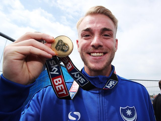 Jack Whatmough displays his League Two title-winning medal at the Southsea Common celebrations in May 2017. Now all that squad have left Pompey. Picture: Joe Pepler
