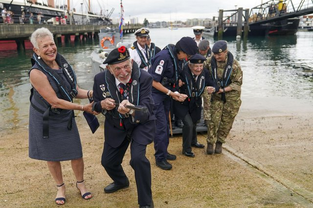 D-Day veteran Joe Cattini raises his walking stick like a machine gun as he and other veterans are welcomed to the Portsmouth Historic Dockyard to commemorate the 77th anniversary of the Normandy Landings. Picture: Steve Parsons/PA Wire