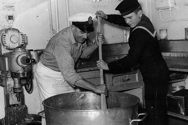 Maureen Maidment envió esta fotografía de su padre y el miembro más joven de la tripulación, Jerry Locke de Portchester, revolviendo el pudín de Navidad con una paleta.  Fue subido a bordo del HMS Maidstone, un buque depósito de submarinos, en diciembre de 1954.