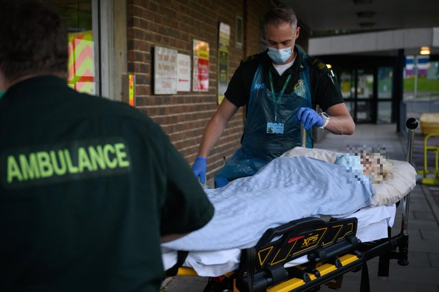An ambulance crew wearing protective clothing transfer a patient, whose condition was described as not being related to Covid-19, from their ambulance to the Queen Alexandra hospital on May 5, 2020. Picture: Leon Neal - Pool/Getty Images