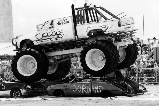The giant White Thunder Monster Truck riding over four cars in the Southsea Show arena, 1993. The News PP5208