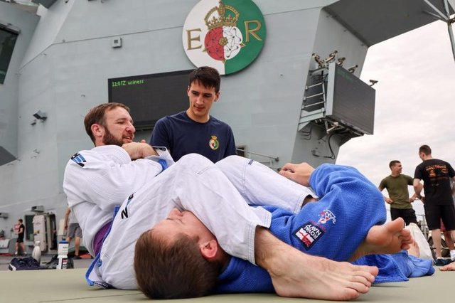 Sailors work on their ground-based skills as one is placed in an arm bar submission hold on HMS Queen Elizabeth. Photo: Royal Navy/Twitter