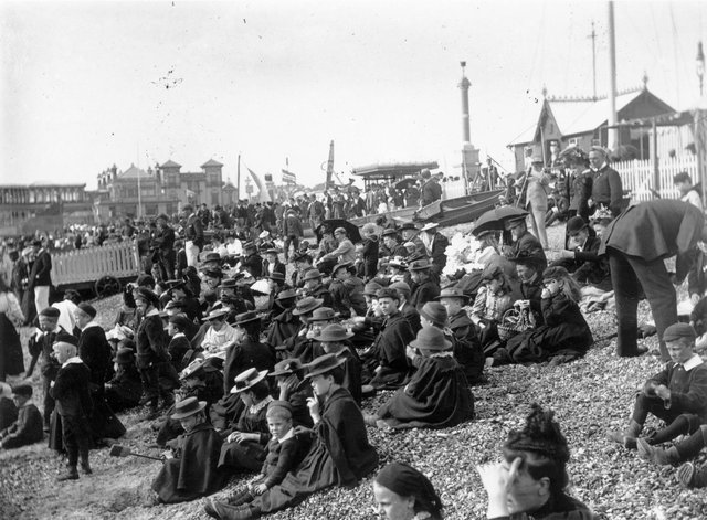 This photo is from circa 1895 and it shows a crowd mainly of children, wearing hats and warm clothing, sit on stony Southsea beach looking out to sea.  Photo by F J Mortimer/Hulton Archive/Getty Images